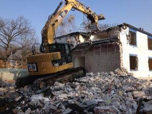 Разрушение стен здания экскаватором