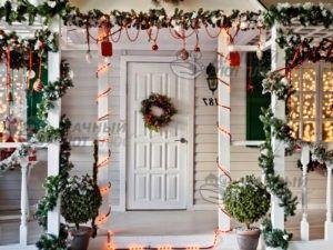 Украшение рождественскими гирляндами входа в дом