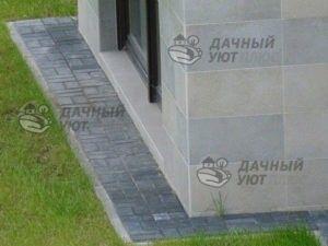 Отмостка из бручсатки, сделанная вокруг стен дома, защищает их от брызг, но не препятствует испарению грунтовой влаги.